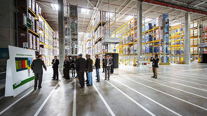 People attending a presentation in the Lidl Distribution Center warehouse lit by Philips Lighting