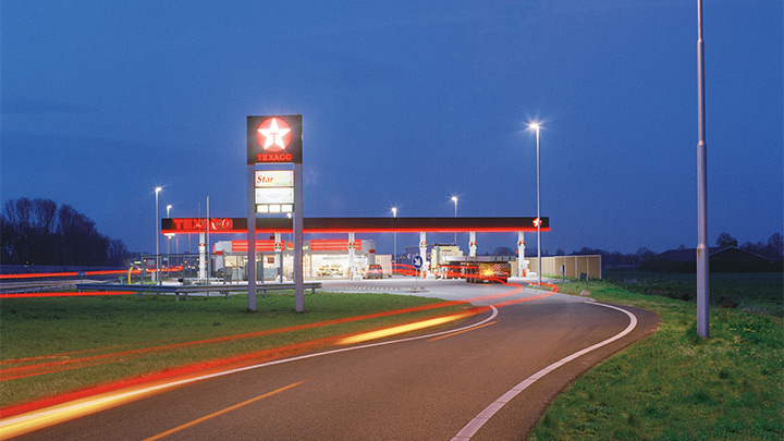 A Texaco gas station off of the highway, attractively illuminated at dusk - eye catching outdoor lighting